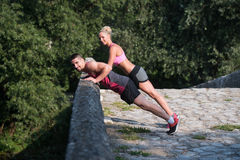Young Couple Doing Pushups Outdoor Stock Image