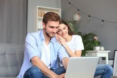 Young couple doing some online shopping at home, using a laptop on the sofa. Young couple doing some online shopping at home, using a laptop on the sofa royalty free stock images