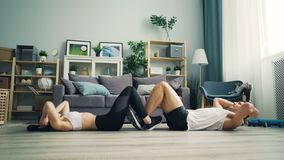 Young couple doing sports together at home exercising abd and clapping hands
