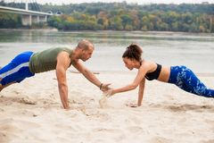 Young couple doing sports training on the beach. Holding hands Stock Image