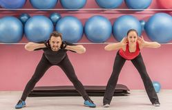 Couple in the Gym. Young couple doing stretching exercises in a gym Royalty Free Stock Photo