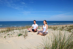 Young couple doing yoga on the beach Royalty Free Stock Photos