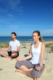 Young couple doing yoga on the beach Stock Images
