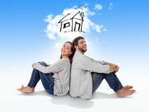 Young couple dreaming and imaging their new house in real state. Young attractive and modern couple in love smiling happy together sitting on floor thinking and Stock Photos