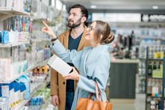 Couple in the pharmacy store. Young couple dressed in coats choosing medicine standing with box in the pharmacy store stock photo