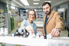 Couple in the pharmacy store. Young couple dressed in coats choosing medicine standing with box in the pharmacy store royalty free stock photo