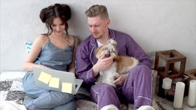 Young couple dressed in pajamas sitting on bed together. stock video footage