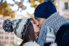 Young couple dressed in winter clothes and wool hats kiss passionately in a public park royalty free stock image