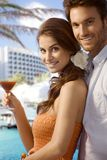 Young couple with drink at luxury beach resort. Young happy casual caucasian couple with cocktail drink at luxury summer beach holiday resort. Standing, smiling Royalty Free Stock Photography