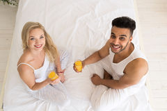 Young Couple Drink Orange Juice Sitting In Bed, Happy Smile Hispanic Man And Woman Top Angle View Stock Photo