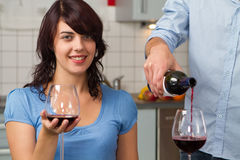 Young couple drink red wine in kitchen Royalty Free Stock Photography