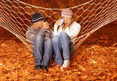 Young couple drink tea in hammock Stock Images