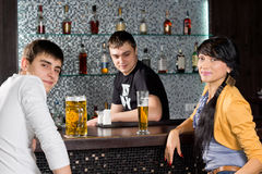 Young couple drinking with the barman at the bar. Young couple drinking at the bar with the barman turning and smiling at the camera as they spend a relaxing royalty free stock photography