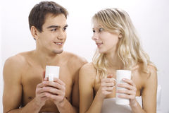 Young couple drinking on the bed in bedroom Royalty Free Stock Photography