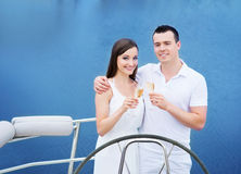 A young couple drinking champagne on a boat Stock Photos