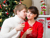 Young couple drinking champagne at Christmas tree Royalty Free Stock Photos