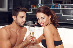 Young couple drinking champagne in jacuzzi Royalty Free Stock Photo