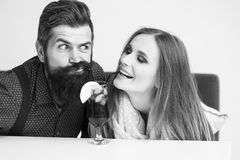 Young couple drinking cocktail. Closeup view on one attractive stylish emotional couple of young women and men with long beard drinking blue cocktail in glass Stock Images