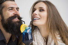 Young couple drinking cocktail. Closeup view on one attractive stylish emotional couple of young women and senior men with long black beard drinking blue Stock Photo