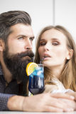 Young couple drinking cocktail. Closeup view on one attractive stylish emotional couple of young women and senior men with long black beard drinking blue Stock Images