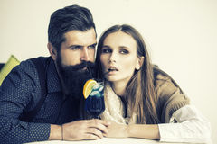 Young couple drinking cocktail. Closeup view on one attractive stylish emotional couple of young women and senior men with long black beard drinking blue Royalty Free Stock Photo