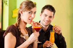 Young couple drinking cocktails. Young happy couple drinking cocktails in bar or restaurant; presumably it is a first date Stock Photo