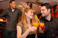 Young couple drinking cocktails in ba. Young happy couple drinking cocktails in bar or restaurant, friends are standing in the background Stock Photography