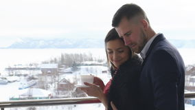 Young couple drinking coffee on the balcony,winter. Young couple drinking coffee on the balcony on a background of mountains and rivers,winter stock video footage