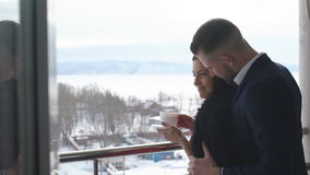 Young couple drinking coffee on the balcony,winter. Young couple drinking coffee on the balcony on a background of mountains and rivers,winter stock video