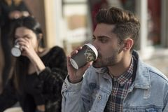 Young couple drinking coffee in bar terrace. Coffee to go stock photography