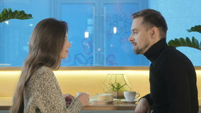 A young couple is drinking coffee in a cafe stock footage