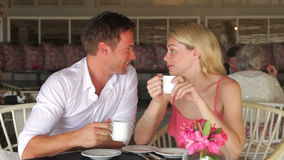 Young Couple Drinking Coffee In Restaurant. Couple sitting in restaurant talking and drinking coffee.Shot on Canon 5d Mk2 with a frame rate of 30fps stock video