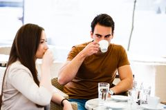 Young couple drinking coffee while sitting at cafe royalty free stock photo
