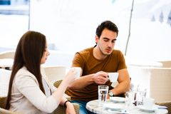 Young couple drinking coffee while sitting at cafe stock images