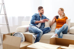 Young couple drinking coffee on sofa Stock Photos