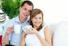 Young couple drinking coffee together on the sofa. And looking the side Stock Photography