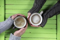 Young couple drinking hot coffee at wooden table on a date Stock Photo