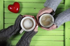 Young couple drinking hot coffee at wooden table on a date Royalty Free Stock Photo