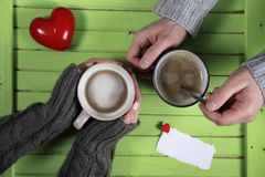 Young couple drinking hot coffee at wooden table on a date Stock Photography