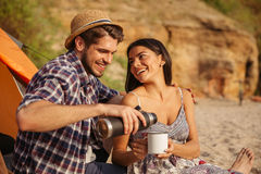 Young couple drinking hot tea at the bonfire while camping. At the beach Stock Image