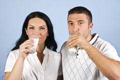 Young couple drinking milk. Cheerful healthy couple drinking milk in front of image,they wear white clothes on blue background,check also my collection Healthy Stock Photography