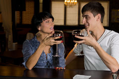 Young couple drinking red wine at a bar counter royalty free stock photo