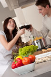 Young couple drinking red wine in kitchen Stock Image