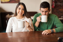 Young couple drinking some coffee in a cafe. Portrait of a cute young women and a male friend drinking some coffee in a restaurant Royalty Free Stock Photo