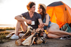 Free Young Couple Drinking Tea At The Bonfire While Camping Royalty Free Stock Photography - 75796657