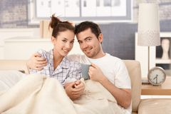 Young couple drinking tea in bed smiling happily Stock Photos