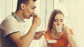 Young couple drinking tea or coffee at home Royalty Free Stock Photo