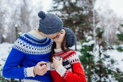Young couple drinking tea and kissing in winter forest. Happy people relaxing outdoors during holidays stock photos