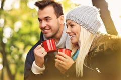 Young couple drinking tea outdoors Stock Photos