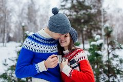 Young couple drinking tea in winter forest. Happy people relaxing outdoors during holidays. Valentines day royalty free stock images